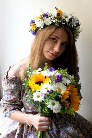 Девушка с букетом подсолнухов и ромашек