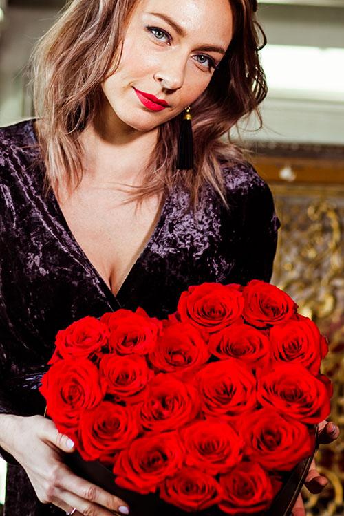 Красивая девушка с красными розами в коробке