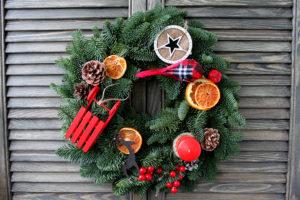 Рождественский венок из пихты, красных санок и свечи