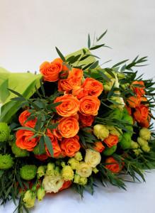 Букет из оранжевых роз, кремовых лизиантусов и зеленых хризантем.