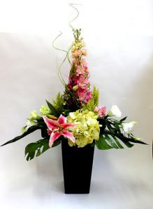Композиция из искусственных цветов в высокой вазе с дельфиниумом.